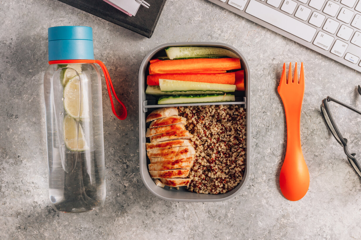 Healthy meal prep containers with quinoa, chicken and and sticks of cucumber and carrots on light gray background. Healthy lunch at work. Take away concept.